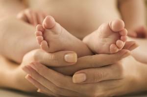 Mother Cradling Baby's Feet --- Image by © Jamie Grill/Corbis
