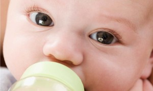 Close up of baby drinking from bottle